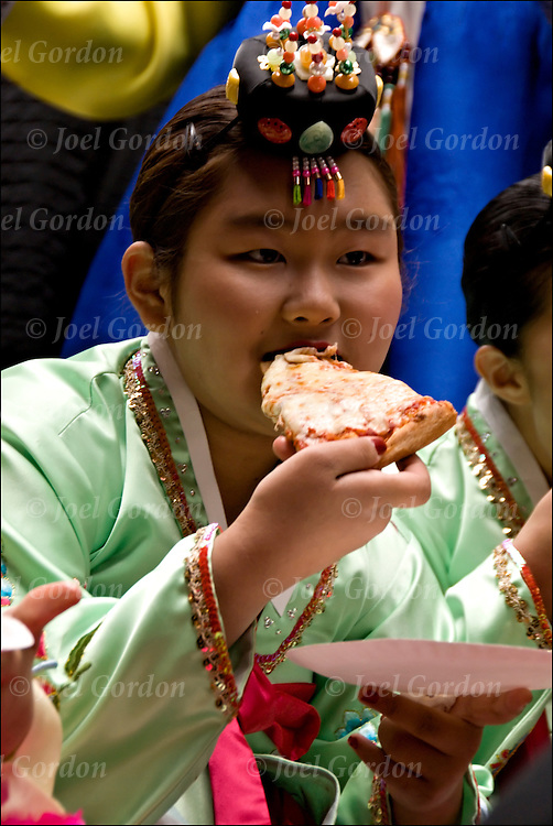 Korean American girl in folk regalia sitting on float eating Pizza before the start of the parade.  The Korean Day Parade is on the first Saturday of October. It is a celebration for the Korean American community in the Northeast to create awareness of therir Korean culture and ethnic pride.