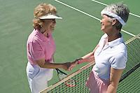 Two women shaking hands over tennis net