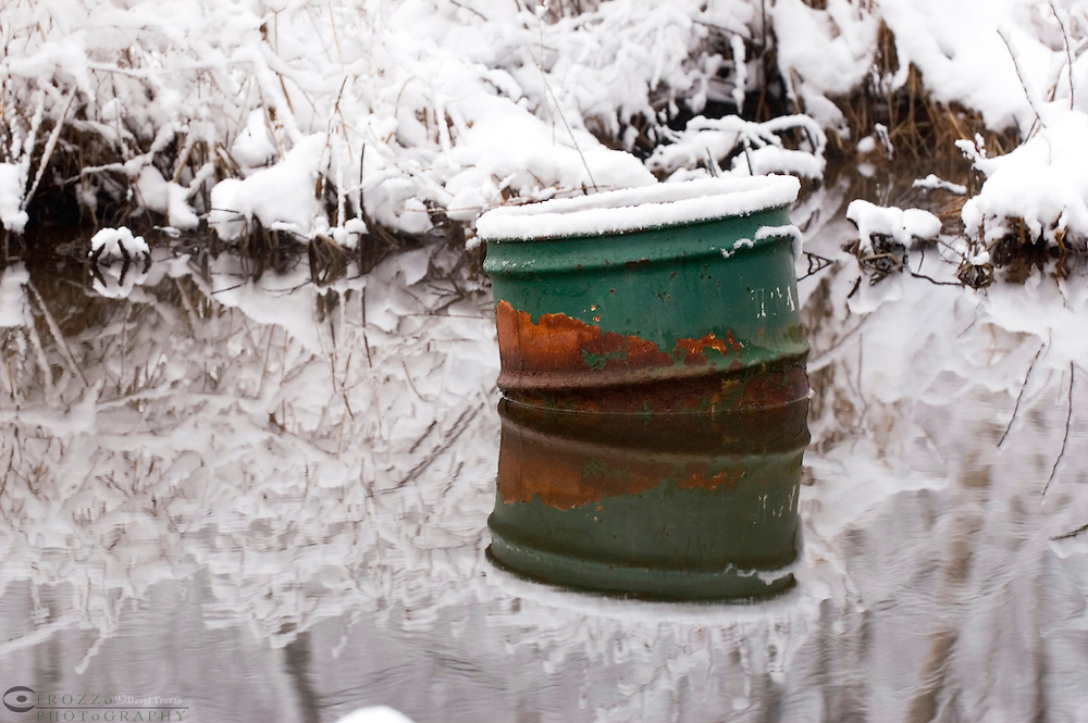 Old metal drum trash can pollutes a creek