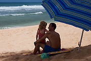 A little girl leans on her dad's shoulder on the beach in Hawaii