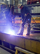 A worker cleans up cuts made by a plasma cutter at Trinity Structural Towers in Newton, Iowa on February 12, 2010.