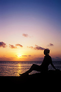 Sillhouette of woman watching the sunset. Ambergris Caye, Belize, Caribbean.