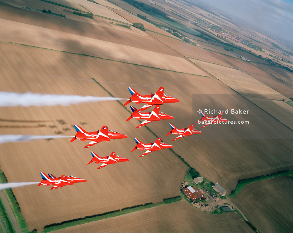 Banking slowly left over the agricultural Lincolnshire countryside are the elite 'Red Arrows', Britain's prestigious Royal Air Force aerobatic team, who have commenced an In-Season Practice (ISP) training flight near their base at RAF Scampton. They turn at a gentle angle trailing white organic smoke  before reforming in front of a local crowd at the airfield and working through a 25-minute series of display manoeuvres that are loved by thousands at summer air shows. Their objective is to appear perfectly spaced from a ground perspective. Freshly-ploughed English fields with properties, roads and hedgerows are seen below. After some time off, spare days like this are used to hone their manual aerobatic and piloting skills before re-joining the air show circuit. Since 1965 they've flown over 4,000 shows in 52 countries.   .