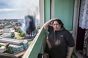 PRESS ASSOCIATION Photo. Picture date: Wednesday June 14, 2017. Local resident Georgina stands distraught on her balcony as the West London tower block burns behind her. A fire was reported at about 01:00 this morning on the 4th floor which engulfed the entire block of residential flats within 20 minutes. <br /> Photo credit should read: Rick Findler/PA Wire