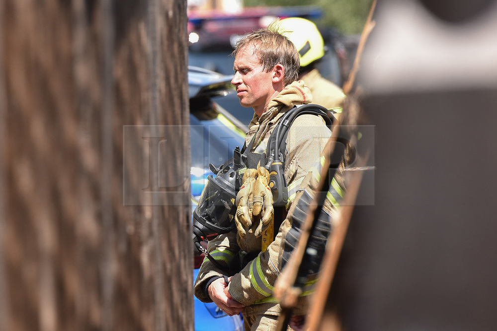 © Licensed to London News Pictures. 16/07/2019. London, UK.  Firefighters prepare to enter the building, with tight access for pumps. Multiple fire engines respond to a fire in a residential block on Bromyard Avenue, in Acton, West London. A black plume of smoke was visible for miles as the penthouse apartment burned. Police helicopters, LBF drones, and paramedics were on the scene in minutes. It is not known at this stage if there were any casualties.  Photo credit: Guilhem Baker/LNP