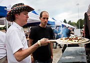 Chris Gragg, left, with Pizza Bruta puts in a fresh pie during the 4th annual Yum Yum Fest held at Breese Stevens Field, Sunday, August 6, 2017.