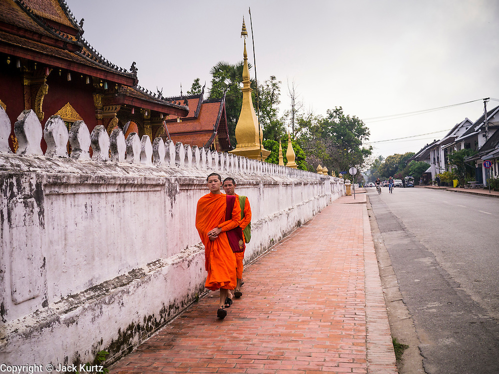 11 MARCH 2013 - LUANG PRABANG, LAOS: Buddhist monks walk along the side of Wat Sensoukaram in Luang Prabang, Laos. Luang Prabang has more than 30 temples and is a UNESCO World Heritage Site. It is the most visited tourist attraction in Laos.    PHOTO BY JACK KURTZ