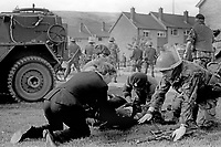 Soldiers, with civilian help, treat an injured colleague during disturbances involving residents of a Roman Catholic public housing estate at Lenadoon Avenue, Suffolk, West Belfast, 9th July 1972. It is alleged the disturbances broke out when Roman Catholics tried to take over public housing in a largely Protestant estate. 197207090379m<br />