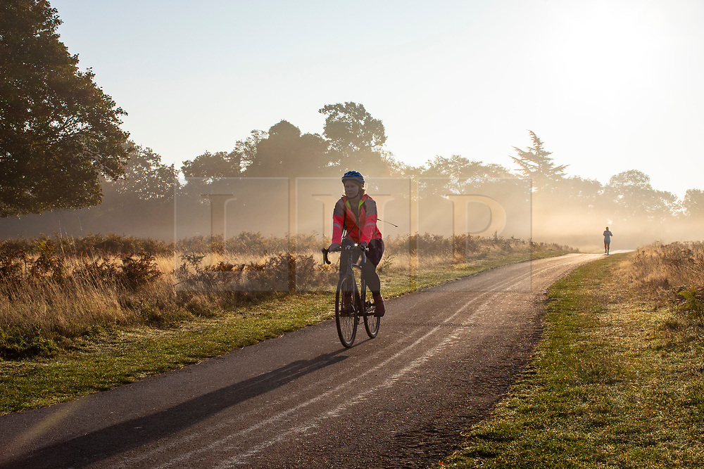 © Licensed to London News Pictures. 10/10/2018. London, UK. Cyclists and joggers at sunrise in Bushy Park, south London. Forecasters are expecting unusually warm temperatures for October. Photo credit: Rob Pinney/LNP