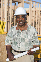 Middle-aged man with blueprints, construction site