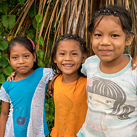 Three young Peruvian girls with their arms around each other in the village of San Francisco off of the Marañon River. Pacaya Samiria National Reserve, Upper Amazon, Peru.