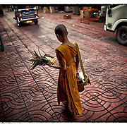 A young novice Buddhist monks on his early morning rounds in the Chinatown section of Bangkok.