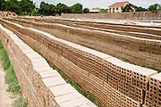 30 JUNE 2006 - PHNOM PENH, CAMBODIA: Stacked up bricks dry in the sun before being put into the kiln at a brick factory in Phnom Penh, Cambodia. According the United Nations Food and Agricultural Organization, there are more than 70 brick factories in Phnom Penh and its environs. Environmentalists are concerned that the factories, most of which burn wood in their kilns, contribute to deforestation in Cambodia. They are encouraging factory owners to switch to burning rice husks, as brick kilns in neighboring Vietnam do. The brick factories are kept busy feeding Phnom Penh's nearly insatiable appetite for building materials as the city is in the midst of a building boom brought by on economic development and the need for new office complexes and tourist hotels.   Photo by Jack Kurtz / ZUMA Press