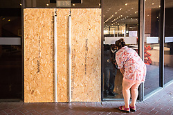 © Licensed to London News Pictures . 17/06/2017 . London, UK . A woman wanting to volunteer her services to help residents speaks to a security guard through a window . Boarded up doors around the entrances to Kensington and Chelsea Town Hall as a planned protest outside is cancelled . Residents and campaigners were due to demonstrate outside the Town Hall following a catastrophic fire that killed dozens in their homes when it engulfed and destroyed the Grenfell Tower block . Grenfell Action Group and Radical Housing Network called the protest after many accused the local council and government of failing to act to provide sufficient support before and in the wake of the fire . Photo credit: Joel Goodman/LNP