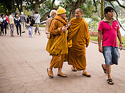 31 MARCH 2012 - HANOI, VIETNAM:  Buddhist monks walk around the shore of Lake Ho Hoan Kiem in the Old Quarter of Hanoi, Vietnam.  PHOTO BY JACK KURTZ