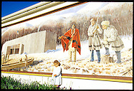 Little girl by outdoor mural depicting Lewis & Clark and Mandan Indian outside Fort Mandan in winter 1804-5; Washburn, N Dakota
