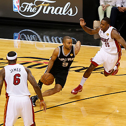Jun 6, 2013; Miami, FL, USA; San Antonio Spurs point guard Tony Parker (9) drives between Miami Heat point guard Mario Chalmers (15) and LeBron James (6) in the first quarter during game one of the 2013 NBA Finals at the American Airlines Arena. Mandatory Credit: Derick E. Hingle-USA TODAY Sports