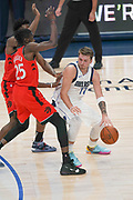 Dallas Mavericks point guard Luka Doncic (77) drives to the basket while being heavily guarded by Toronto Raptors power forward Chris Boucher (25) and Rondae Hollis-Jefferson (4) during an NBA basketball game, Saturday, Nov. 16, 2019, in Dallas. The Mavericks defeated the Raptors 110-102. (Wayne Gooden/Image of Sport)