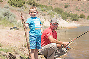 Father and son smile while fishing together on Lower Goose Creek Reservoir near Oakley, Idaho.