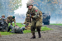 A Re-enactor portrayiing a member of the 82nd All American Airborne Division carrying a Browning Automatic Rifle (BAR) advances on crumbling German positions during a battle battle re-enactment in on Pickering Showground<br /> <br /> 17/18 October 2015<br />  Image © Paul David Drabble <br />  www.pauldaviddrabble.co.uk