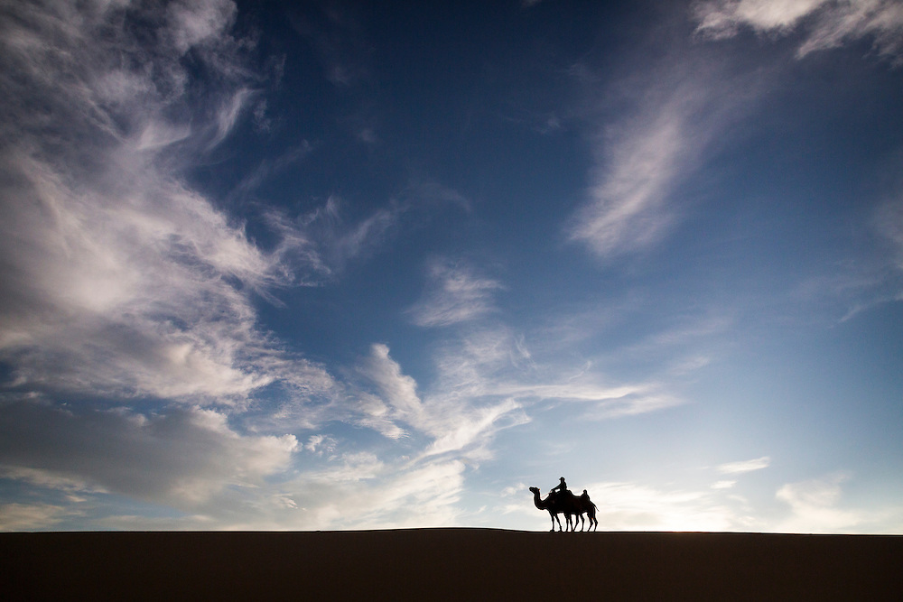 A Mongolian woman rides a camel over a sand dune in the Gobi Desert on July 28, 2012. © 2012 Tom Turner Photography