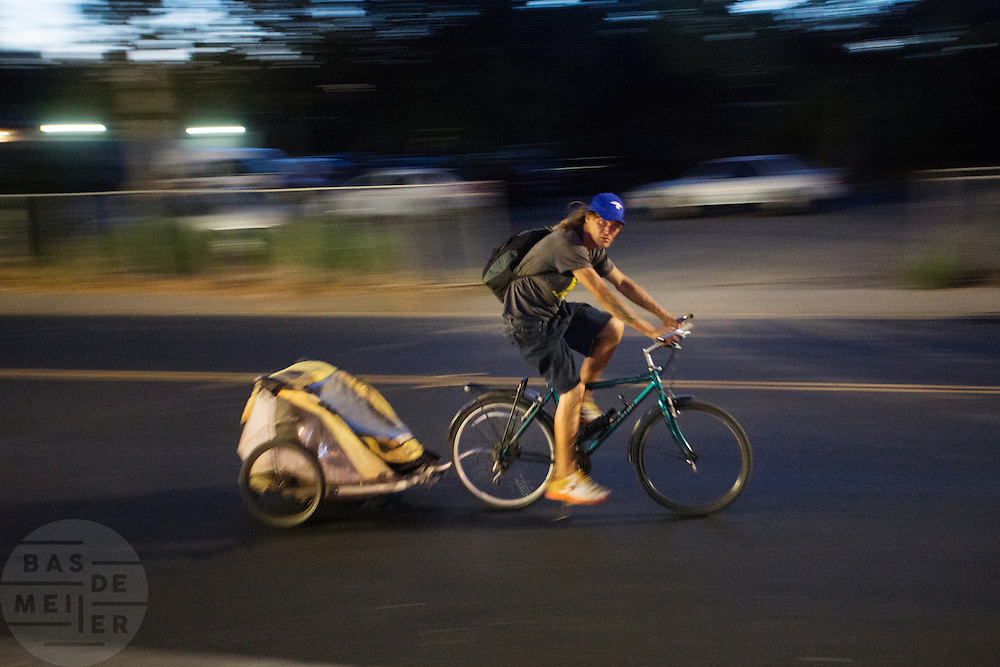 In de Amerikaanse plaats Davis, California fietst een man met een fietskar door de avond.<br /> <br /> In the American town Davis, California cyclists ride in the evening with a trailer.