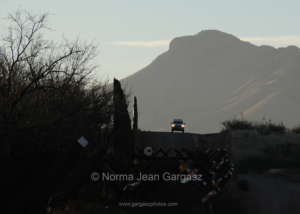 A U.S. Border Patrol agent drives along the metal fence that divides Arizona and Mexico near the property of Glenn Spencer of the American Border Patrol, Hereford, Arizona, USA.
