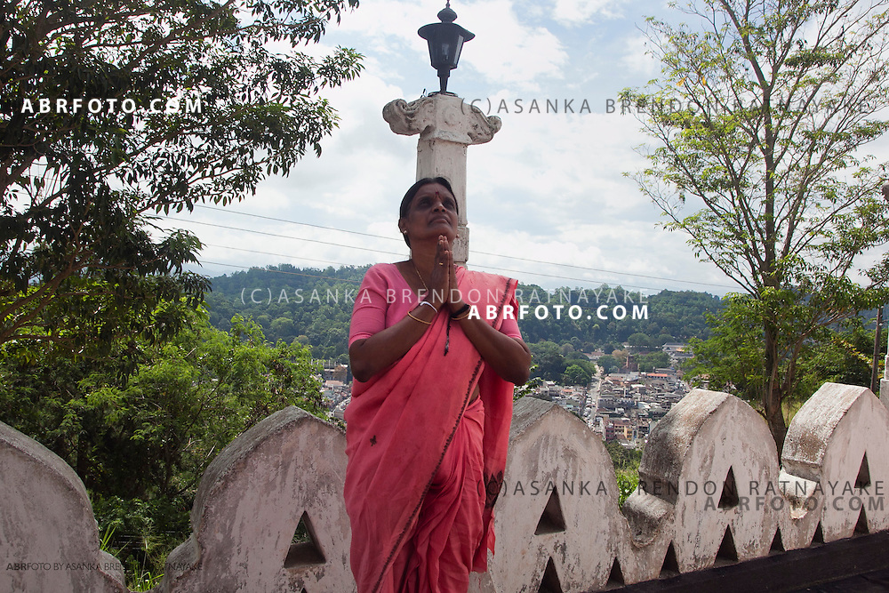 a devotee prays towards the large lord Buddha statue at A young monk plays cricket at the top of Bahirawakanda temple in Kandy.