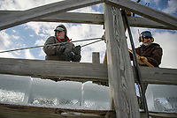Bruce Whitmore and Eric Morse work on the lift as they load 150 lb ice blocks during the annual Rockywold Deephaven Camp ice harvest on Tuesday.  ©2018 Karen Bobotas Photographer