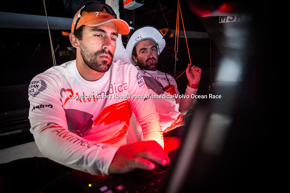 January 18, 2015. Day 15 of Leg 3 to Sanya, onboard Team Alvimedica. Windy upwind conditions make the last 100 miles to Sumatera and the corner of the Malacca Strait rough and wet. Mark Towill (L) and Charlie Enright (R) at work in the nav station, discussing the options for entrance to the Malacca Strait.