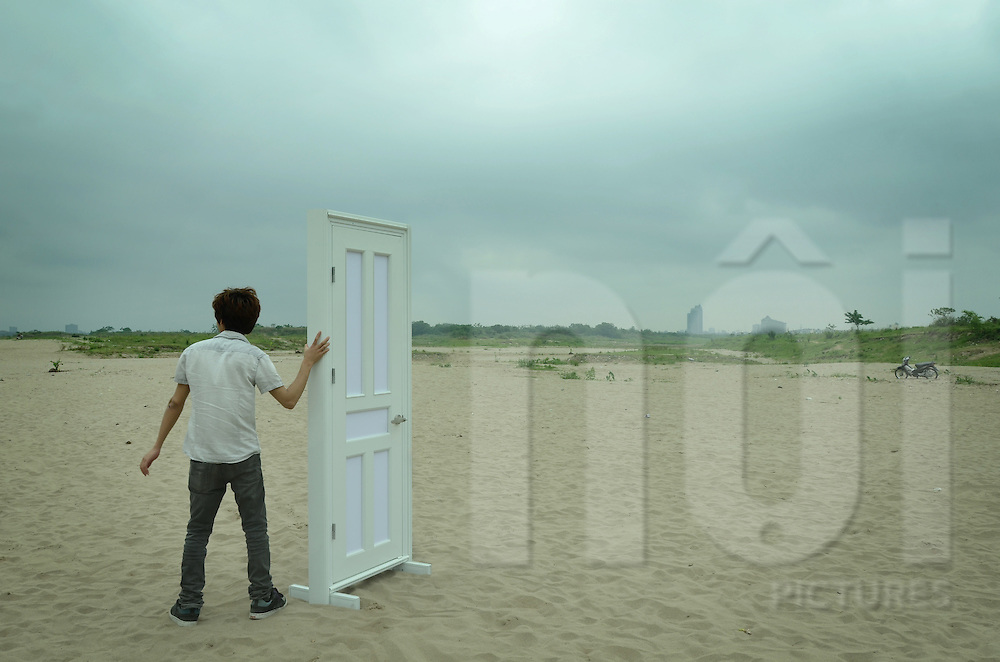 Surreal scene of a Vietnamese man holding a white door standing on a deserted sandy beach near the Red River, Hanoi, Vietnam, Southeast Asia