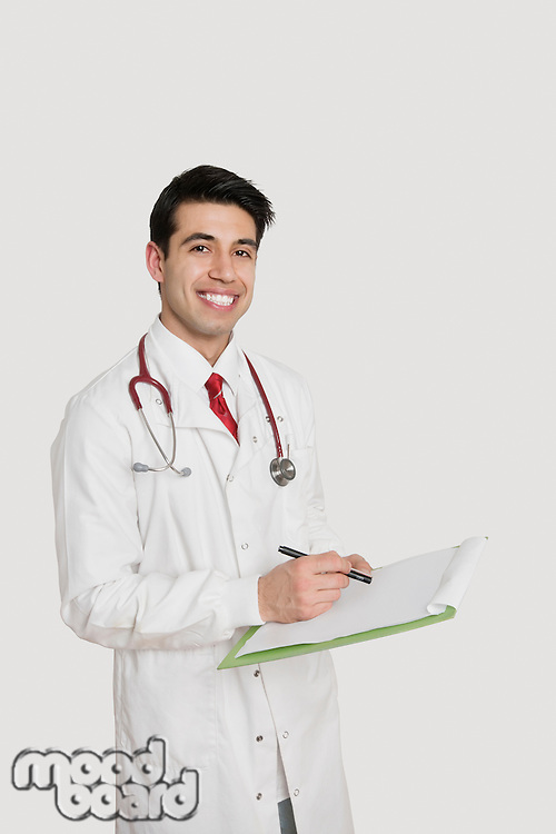 Portrait of a cheerful Indian male doctor holding a medical chart over light gray background