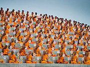 "22 FEBRUARY 2016 - KHLONG LUANG, PATHUM THANI, THAILAND:  Buddhist monks sit around the chedi during Makha Bucha Day at Wat Phra Dhammakaya.  Makha Bucha Day is a public holiday in Cambodia, Laos, Myanmar and Thailand. Many people go to the temple to perform merit-making activities on Makha Bucha Day, which marks four important events in Buddhism: 1,250 disciples came to see the Buddha without being summoned, all of them were Arhantas, Enlightened Ones, and all were ordained by the Buddha himself. The Buddha gave those Arhantas the principles of Buddhism, called ""The ovadhapatimokha"". Those principles are:  1) To cease from all evil, 2) To do what is good, 3) To cleanse one's mind. The Buddha delivered an important sermon on that day which laid down the principles of the Buddhist teachings. In Thailand, this teaching has been dubbed the ""Heart of Buddhism."" Wat Phra Dhammakaya is the center of the Dhammakaya Movement, a Buddhist sect founded in the 1970s and led by Phra Dhammachayo.     PHOTO BY JACK KURTZ"
