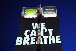 "© Licensed to London News Pictures. 05/07/2020. London, UK.  A light projection reading 'WE CAN'T BREATHE' is cast onto the shell of Grenfell Tower in West London on the eve of the second phase of the Grenfell Tower Fire Inquiry. The slogan echoes the words spoken on the night recorded on calls to emergency services and loved ones begging for help that never came. <br /> Abbas Dadou, Chairman of Lancaster West Estate Residents Association comprising 800 homes and 2000 residents said ""We stand in solidarity with the families who lost their loved ones in their fight for justice. They are us and we are with them. They are part of our community and their fight for justice is our fight."" El  Alami Hamdan who lost his daughter and his grandchildren in the fire said ""how long must we wait for justice? It has been three years and still nothing. They promise everything and they do nothing.'  <br /> <br /> A press conference will be held this morning ahead of the Inquiry resuming, where the following statement will be released at 10am:<br /> 'Family members of those who perished in the fire that took the lives of 72 people on June 2017 were present last night when the projection of 'We can't breathe' was cast on the now iconic building ""These words echo what we heard on the 999 calls of our loved ones, or the last final breath taken by our brothers and sisters, mothers and fathers and our children that night as they begged for help. We have had to listen to these calls as part of the Inquiry going through the pain of their suffering and the complete failures which cost our loved ones' tragic deaths that night.  We are no longer going to keep silent. We demand justice. We want prosecutions. We are not willing to wait as these words echo in our heads everyday. It is heartbreaking but this projection is also a powerful message from us to the authorities that we will be heard. When we think of what family members went through that night, all we hear is 'we can't breathe.  All we imagine is"