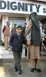 A Kashmiri woman covered in a burqua and her son pass through a security check point during Ramadan in Srinagar, the summer capital of the state of Kashmir in India, November 20, 2001.  Kashmir has seen over 900 civilians killed this year and 1,765 wounded in a brutal conflict that the United Nations calls the most dangerous place in the world.  (Photo by Ami Vitale/Getty Images)