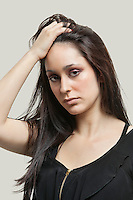 Portrait of young woman with hand in hair against gray background