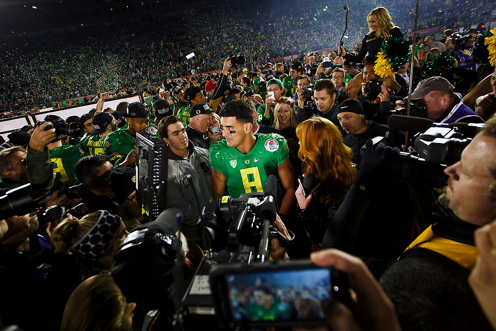 Oregon quarterback Marcus Mariota (8) is surrounded by people after the game. The No. 2 Oregon Ducks play the No. 3 Florida State Seminoles at the Rose Bowl Stadium in Pasadena, California on January 1, 2015. (Ryan Kang/Emerald)