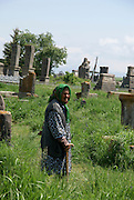 Armenia, Lake Sevan, Noraduz cemetery Local woman sells souvenirs to tourists