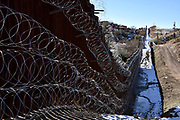 Four rows of concertina wire cover the metal wall in Nogales, Arizona, USA, at the international border with Nogales, Sonora, Mexico.