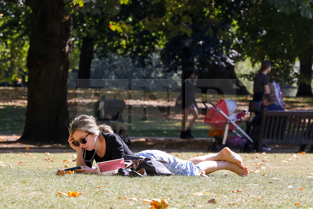 © Licensed to London News Pictures. 13/09/2019. London, UK. A woman reads a book in St James's Park on a warm and sunny day in the capital. According to the Met Office, the temperature is likely to reach 25 degrees celsius this weekend in many parts of UK. Photo credit: Dinendra Haria/LNP