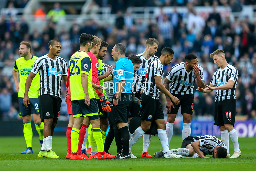 Tommy Smith (#2) of Huddersfield Town and Jonas Lossl (#1) of Huddersfield Town argue with referee Kevin Friend after Tommy Smith (#2) of Huddersfield Town is shown a red card for a foul on Miguel Almiron (#24) of Newcastle United during the Premier League match between Newcastle United and Huddersfield Town at St. James's Park, Newcastle, England on 23 February 2019.