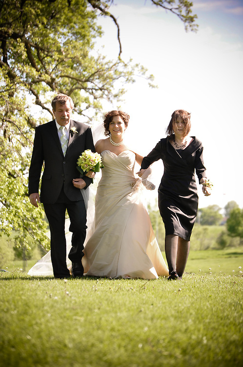 Abby's parents walk her down the isle at Sticks in Des Moine, IA