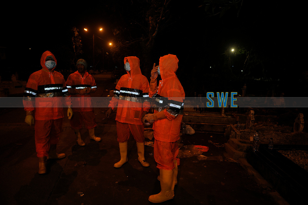 Medan, Indonesia, March 25, 2020: Indonesian social volunteer grroup (local residents) seen on preparing to bury a dead body victims of Corona Virus Disease (COVID) 19 spread of Medan in a public cemetery in North Sumatra province, Indonesia on March 25, 2020.