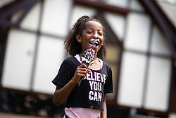 © Licensed to London News Pictures . 26/07/2018. Manchester , UK . ITALEE ANDERSON (eight, correct, from Moss Side) enjoys an Oreo Ice Cream in Alexandra Park . People enjoy the summer sunshine in Manchester as temperatures in the UK are forecast to break records . Photo credit : Joel Goodman/LNP