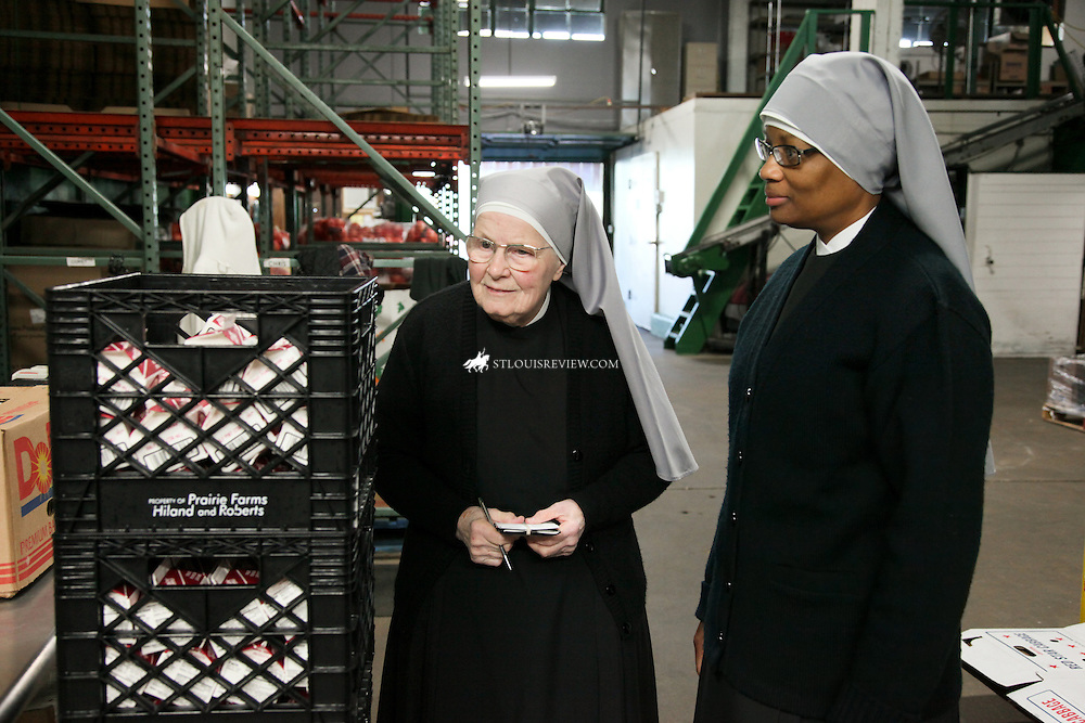 Sister Irene Marie Claire and Sister Emmanual Maria Talley look over cartons of soon to expire iced tea that was donated while the sisters toured produce row.