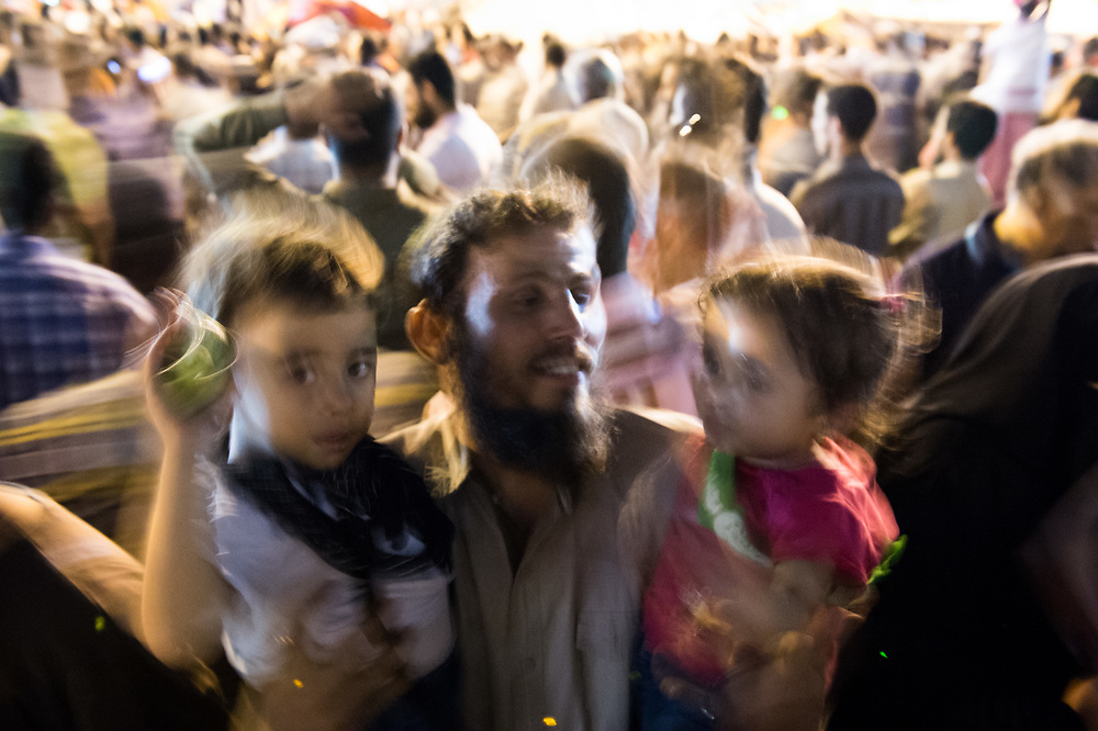 A supporter of ousted president Morsi holds his two children in the arms during a sit-in on Rabaa Al-Adawiya Square in Cairo, Egypt, July 5, 2013