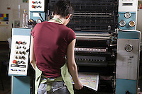 Young woman operating printing press
