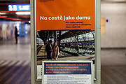 Prague Main Railway Station (Hlavni Nadrazi) during an early Wednesday morning.  Advertisement for the Czech railway (in the back) and a warning sign and how to behave instructions after the Coronavirus pandemic (COVID-19) outbreak - pictured on the 11th of March 2020.