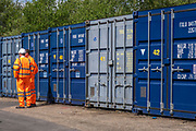 Two men dressed in orange high-visibility work clothes stand next to a row of blue metal storage shipping containers in a self-storage depot in Aldershot, Hampshire, UK.  (photo by Andrew Aitchison / In pictures via Getty Images)