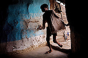 Sachin, 14, a child with a severe physical disorder affecting his bone structure and legs, is entering his home in the impoverished Oriya Basti Colony in Bhopal, Madhya Pradesh, near the abandoned Union Carbide (now DOW Chemical) industrial complex.